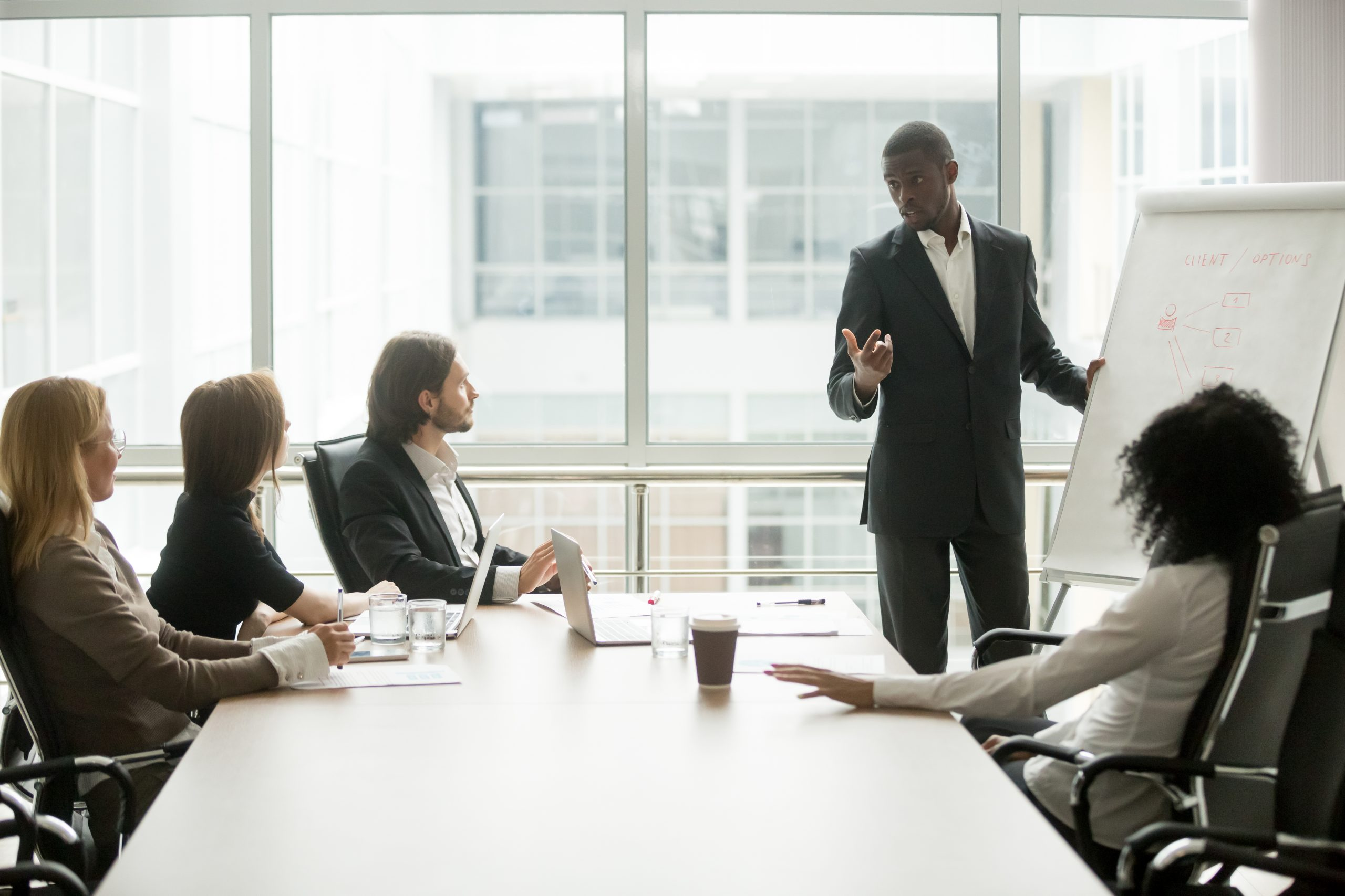 Black coach giving presentation to clients at conference meeting